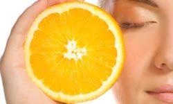 Mujer con la cara cerca de naranja.