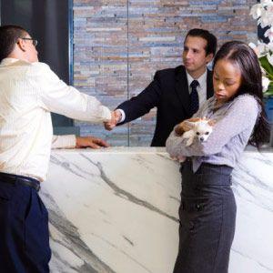Hombre joven estrechando la mano con una recepcionista y una mujer joven sosteniendo un cachorro