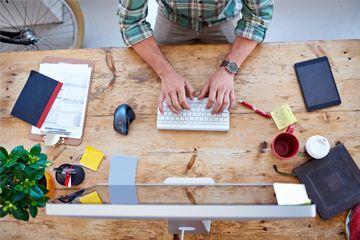 Hombre que pulsa en el ordenador en el escritorio