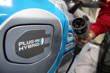Un miembro del personal de Toyota tiene un enchufe de carga junto a un Toyota Prius Plug-in Hybrid EV en Japón, en Tokio.
