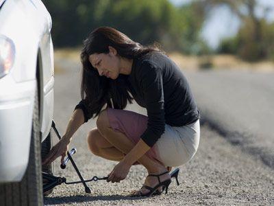 Mujer que cambia neumático desinflado utilizando gato del coche.