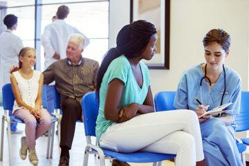 Un médico examina el papeleo con un paciente en una sala de espera.