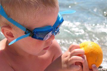 niño en gafas de natación que sostiene una naranja