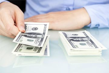 Una persona contando dinero en efectivo.
