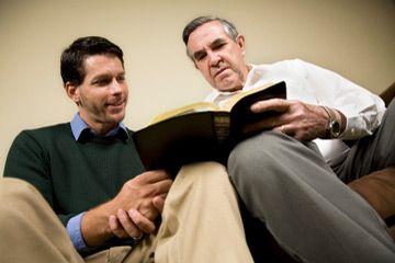 Dos hombres leyendo juntos.