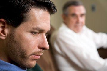 Hombre de mirada triste que otro observa.