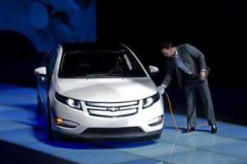 Un miembro del personal de GM China cobra hasta un Chevrolet Volt durante una ceremonia para enviar un par de voltios a Shanghai Oficina Expo en Shanghai, China.