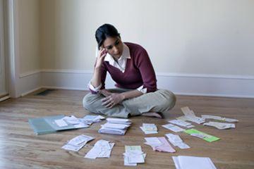Una mujer mirando las facturas y recibos en el suelo.