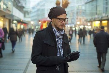 Hombre urbano tomando notas en su computadora de la tableta en la calle.