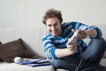 Hombre usando los controles de juego de ordenador sentado en el sofá.