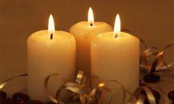 Tres velas con cinta de oro y bolas de color rojo, vertical