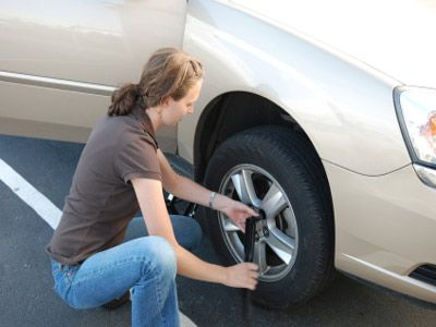 Mujer que cambia rueda pinchada.