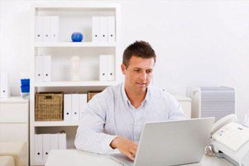 Hombre de negocios que trabaja en el ordenador portátil en casa.