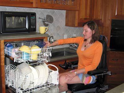 mujer en silla de ruedas utiliza la cocina accesible