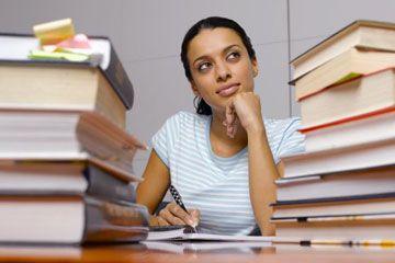 Mujer meditando en medio de los libros de texto