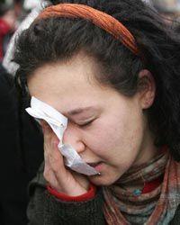 Un manifestante se recupera de un ataque de gas pimienta exterior de una oficina de empleo en Berlín, Alemania.