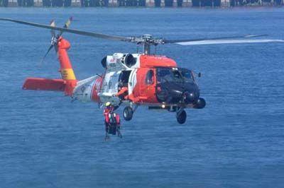Un HH-60 Jayhawk helicóptero de la Guardia Costera de la estación aérea Astoria, Oregón, recupera un nadador de rescate durante un rescate de perforación de recogida.