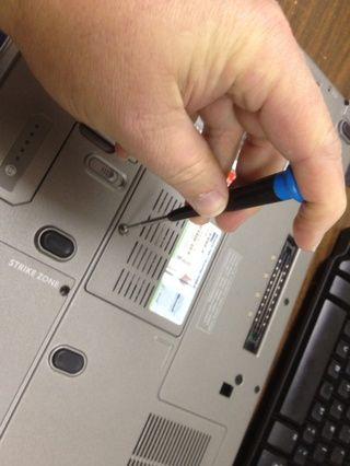 Utilizando el pequeño destornillador Phillips, afloje el tornillo (s) que sujetan la cubierta del módulo de memoria a la computadora portátil.