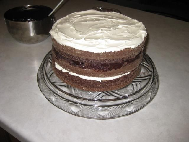 Cubra la segunda capa con con ganache de chocolate y la tercera capa con el relleno fresco látigo. A continuación, poner la última capa de pastel en la parte superior.