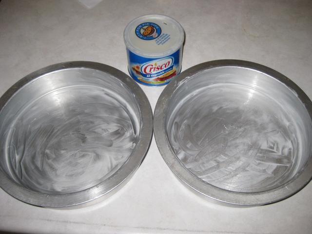 Tomar 2 moldes para pasteles y cubrir completamente con Crisco.