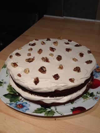 Extender la crema batida entre las capas y en la parte superior de la torta. Decorar con paces nogal.
