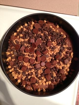 Corre la mantequilla de maní / chips de chocolate y tazas de mantequilla de maní de mini sobre la corteza brownie. Reduzca la temperatura del horno a 325 ° F / 165 ° C.