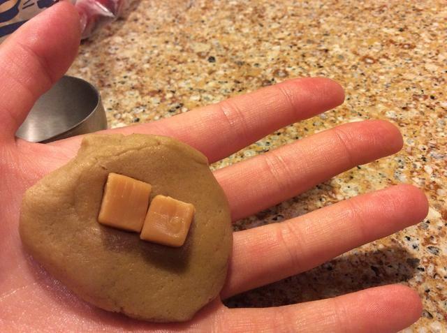 Mide aproximadamente 1 1/2 cucharadas de la masa en una bola. Acoplar el balón con la palma de su mano, luego coloque una de las piezas de caramelo en el centro. Envuelva la masa completamente alrededor de la plaza.