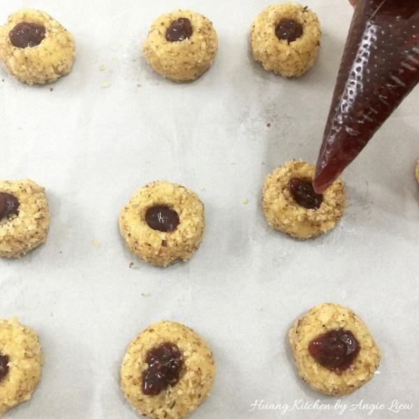 Llene cada muesca con la mermelada de frambuesa con una pequeña cuchara o una manga pastelera lleno. No llene demasiado, sólo un poco por encima de la muesca para que no fluya por los lados cuando se hornea.
