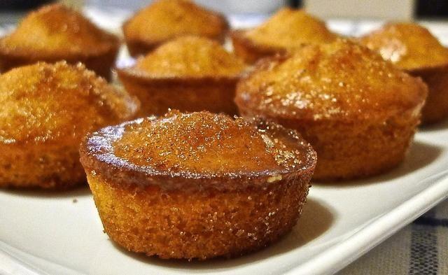 Sumerja la parte superior de donuts en la mantequilla derretida y luego en azúcar con canela.