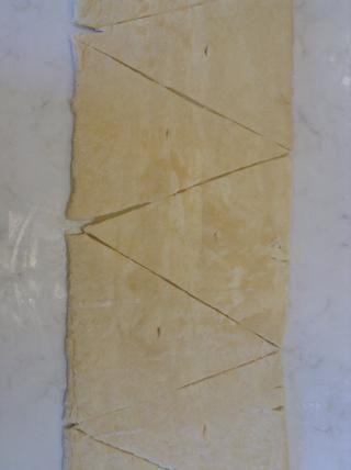Ahora conecte las muescas de los lados derecho e izquierdo para hacer triángulos. Separar los triángulos. Ahora hace un corte en el lado plano inferior del rectángulo para hacer la forma de croissant reconocible.