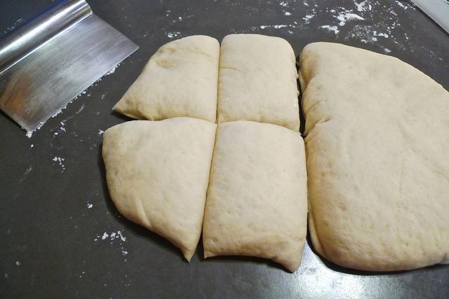 Cortar la masa rectangular en medio. Cortar cada mitad en 4 partes iguales. Un medio para hacer panes de hamburguesa. La otra mitad para hacer panes para perros calientes. (O hacer todas 8 panes de hamburguesa o 8 panes para perros calientes)