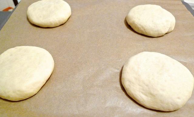 Acaricie suavemente y estirar las rondas de masa en disco plano da forma a cerca de 1/2 pulgada de espesor. Organizar bollos en la hoja de hornear.