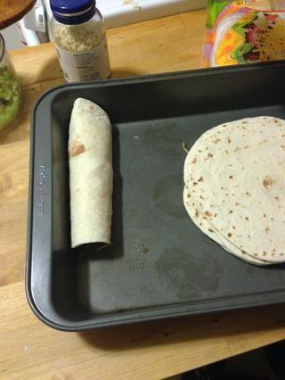 Enrolle la tortilla y poner en la sartén. Repita hasta que se le acaba el pollo. He utilizado un medio de harina y la mitad de las tortillas de maíz.
