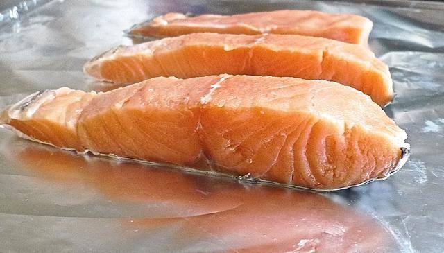 Coloque los filetes de salmón lado de la piel hacia abajo en el plato para hornear forrada.