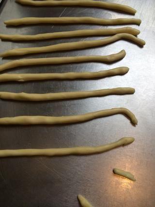 Mientras tanto preparar la masa para los cruces. Mezclar 75 g de flores + 40 g de mantequilla + 1 o 2 cucharadas de agua. Refrigere durante 1 hora y luego hacer 12 cuerdas de largo delgadas.