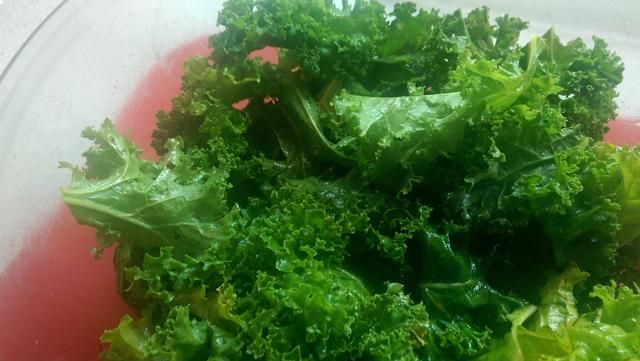 Continuar mezclando puñados de col rizada hasta que've used up 1/2 of the washed kale. Really massage that oil evenly into all the leaves.