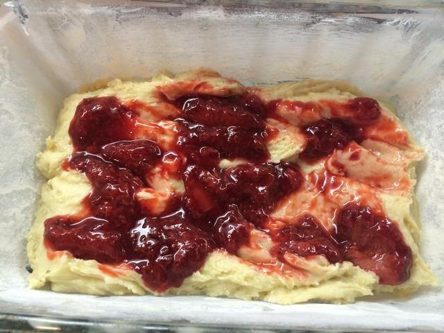 4. Vierta un poco de la mezcla en el molde para pan preparado, que cubre la parte inferior. Mezcla de fresas cuchara sobre la masa, luego cubrir con el resto de la masa. Agitar la mezcla de fresa y batir ligeramente con cuchara