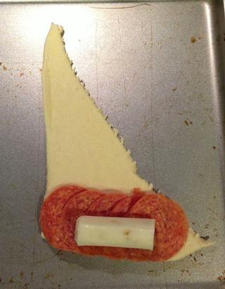 Estirar los rollos de media luna y colocar 4-5 pepperoni en el final, a continuación, coloque 1/2 de un palo queso encima.