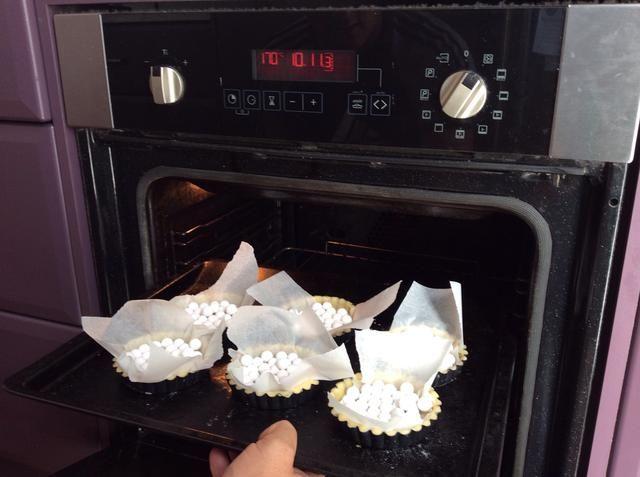 Tome la pastelería de nevera, poner papel de hornear en cada tarta y colocar las bolas de peso en la parte superior. Cocine en 170 por 10 minutos.