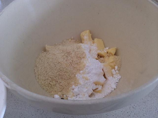 Cortar la mantequilla en trozos pequeños, añadir el azúcar glas, la harina de almendra y poner en un bol.