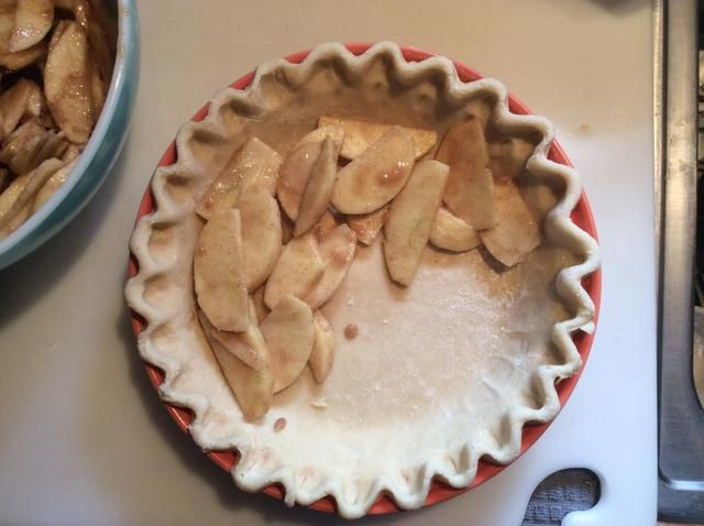Capa de las manzanas en el molde para pastel preparado.