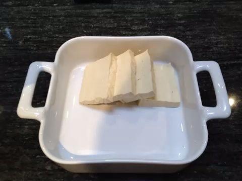 Obtener un recipiente y colocar el queso de soja en la parte superior de uno al otro para que pueda aplicar fácilmente la salsa y dejar marinar.