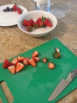 Tops de corte de fresa fuera entonces cortan por la mitad.
