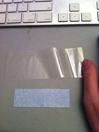 Corta un trozo de cinta adhesiva un poco más largo que su pedacito de papel, y lo pondré pegajoso hacia arriba.