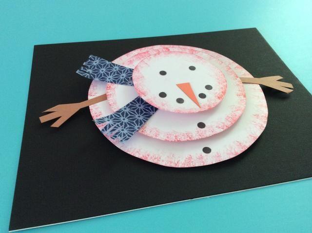 Pegue la nariz naranja y puntos negros de la parte superior del muñeco de nieve.