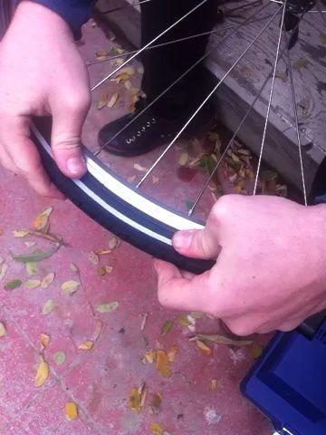 rellenar el segundo talón del neumático en la llanta. tenga cuidado de no pellizcar la cámara entre la llanta y el talón del neumático.