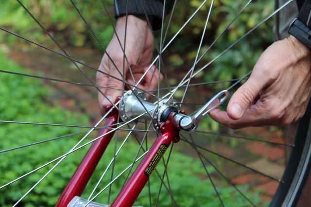 Afloje la bisagra de liberación rápida (o, en motos de mayor edad, los frutos secos) en el centro de la rueda y tomar el volante del cuadro de la bicicleta. Si se's the rear wheel, lift or move the chain away from the gears.