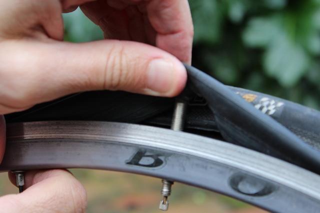 Cuando haya aflojado el neumático de la llanta suficiente para llevarlo a cabo, empujar el vástago de la válvula a través del agujero en el neumático, y tirar de todo el tubo hacia fuera del neumático.