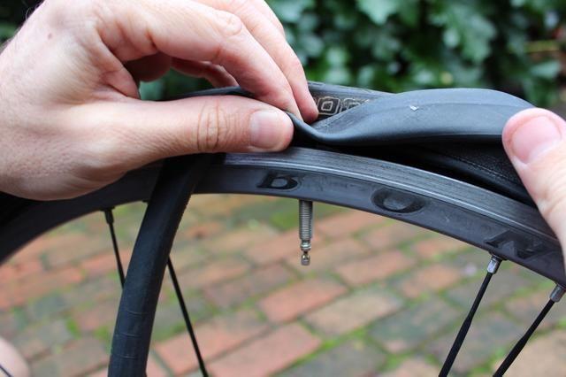 Empuje el vástago de la válvula del nuevo tubo a través del agujero en el neumático y el hilo de todo el tubo alrededor del interior del neumático. Evite torcer el tubo insertándolo como rotundamente posible.