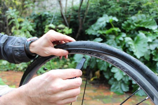 Cuando se hace demasiado difícil de lograr con sólo sus manos, usar su palanca de nuevo hasta que el neumático es nuevo bajo el borde - en ambos lados de la rueda.